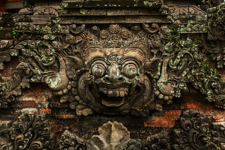 Traditional demon guard statue carved in stone in Bali island.