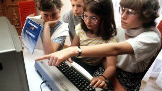 Adolescents try out a Commodore 64 in Nuremberg in May 1985.