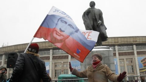 A woman dances in front of a monument of Soviet State founder Vladimir Lenin, after a rally to support presidential candidate and Russia's current Prime Minister Vladimir Putin, outside the Luzhniki stadium on the Defender of the Fatherland Day in Moscow February 23, 2012. Russia will go to the polls for a presidential election on March 4.  REUTERS/Sergei Karpukhin  (RUSSIA - Tags: POLITICS ELECTIONS ANNIVERSARY MILITARY)