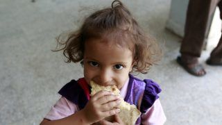 """A displaced Yemeni child, who fled Saada province with her family due to fighting between Shiite Huthi rebels and forces loyal to Yemen's exiled President Abedrabbo Mansour Hadi, eats bread at a school turned into a shelter in the capital Sanaa on August 19, 2015. The United Nations warned of a """"developing famine"""" in Yemen, where more than half a million children are severely malnourished, and pressed for access to its war-torn regions. AFP PHOTO / MOHAMMED HUWAIS / AFP PHOTO / MOHAMMED HUWAIS"""