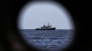 """This picture photo taken on August 13, 2017 shows a banner that reads 'Stop Human Trafficking' attached to the side of the C-Star vessel as it sails in the Mediterranean Sea, 20 nautic miles off the Libyan coast.   The C-Star, is a vessel chartered by a group of European far-right activists opposed to migrants. The activists' """"Defend Europe"""" scheme was launched by anti-immigration campaigners from France, Italy and Germany who raised 170,000 euros ($200,000) via crowd-funding to hire the vessel. / AFP PHOTO / Angelos Tzortzinis"""