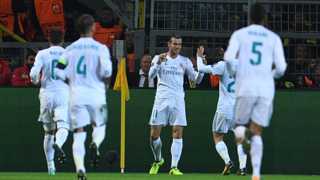 Real Madrid's forward from Wales Gareth Bale (C) celebrates scoring the opening goal with his teammates during the UEFA Champions League Group H football match BVB Borussia Dortmund v Real Madrid in Dortmund, western Germany on September 26, 2017. / AFP PHOTO / Patrik STOLLARZ