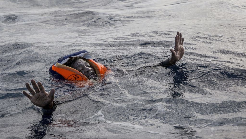 A migrant tries to board a boat of the German NGO Sea-Watch in the Mediterranean Sea on November 6, 2017. During a shipwreck, five people died, including a newborn child. According to the German NGO Sea-Watch, which has saved 58 migrants, the violent behavior of the Libyan coast guard caused the death of five persons.   / AFP PHOTO / Alessio Paduano