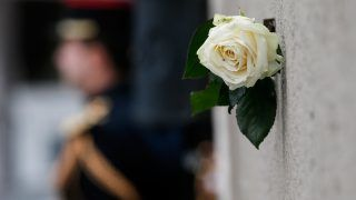 A white rose hangs near a commemorative plaque facing the 'Le Carillon' bar and 'Le Petit Cambodge' restaurant during a ceremony marking the second anniversary of the Paris attacks of November 2015 in which 130 people were killed, in Paris on November 13, 2017.  / AFP PHOTO / POOL / Etienne LAURENT