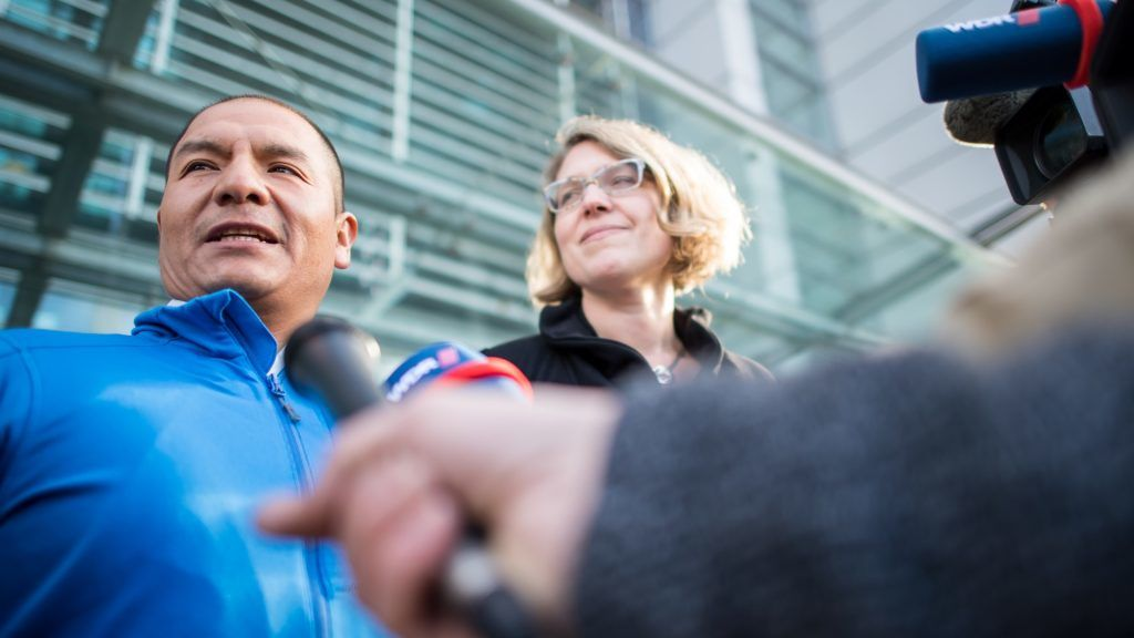 """Peruvian farmer Saul Luciano Lliuya stands next to his lawyer Roda Verheyen as he gives an interview outside the higher regional court of Hamm, western Germany, where the hearing of an appeal began on November 13, 2017. Saul Luciano Lliuya accuses German energy giant RWE of contributing to climate change that is threatening his home and livelihood in the Andes. A lower court in the western city of Essen where RWE is based dismissed the initial lawsuit in December 2016, ruling that Luciano had failed to demonstrate a direct link between the German utility and the flood risk. Luciano, who is also a mountain guide, is now hoping the higher court in the city of Hamm will side with him in what German media have likened to a """"David versus Goliath"""" battle.  / AFP PHOTO / dpa / Guido Kirchner / Germany OUT"""