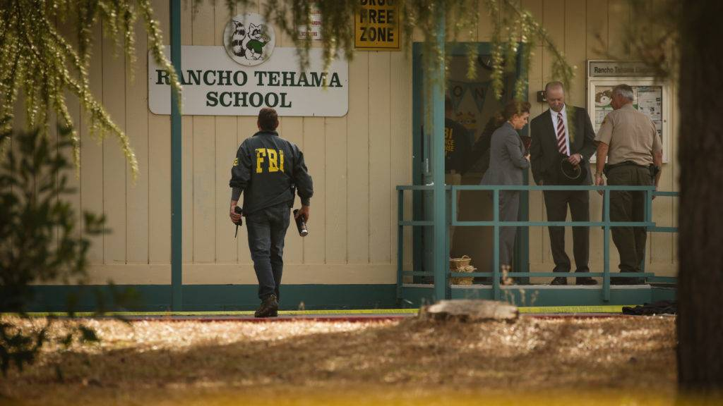 FBI agents are seen behind yellow crime scene tape outside Rancho Tehama Elementary School after a shooting in the morning on November 14, 2017, in Rancho Tehama, California Four people were killed and nearly a dozen were wounded, including several children, when a gunman went on a rampage at multiple locations, including a school in rural northern California. / AFP PHOTO / Elijah Nouvelage