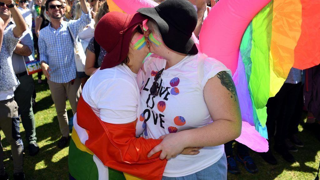 """A couple embrace as supporters of the same-sex marriage """"Yes"""" vote celebrate the announcement in a Sydney park on November 15, 2017. Australians voted in favour of allowing same-sex couples to marry, official results showed on November 15, sending the task of legalising marriage equality to a deeply divided parliament. / AFP PHOTO / WILLIAM WEST"""