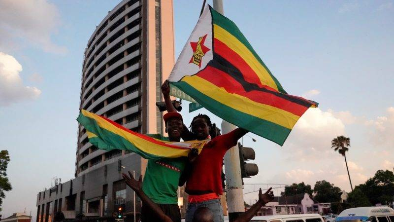 People and soldiers celebrate after the resignation of Zimbabwe's president Robert Mugabe on November 21, 2017 in Harare. Car horns blared and cheering crowds raced through the streets of the Zimbabwean capital Harare as news spread that President Robert Mugabe, 93, had resigned after 37 years in power. / AFP PHOTO / Marco Longari