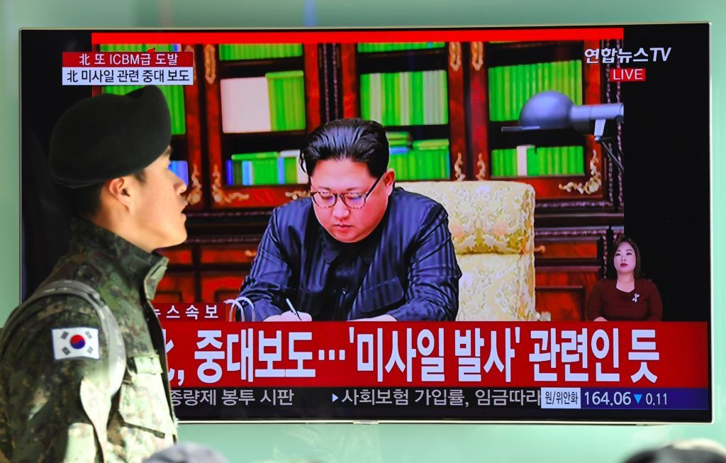 """A South Korean soldier walks past a television news screen showing North Korean leader Kim Jong-Un approving the country's new ICBM test, at a railway station in Seoul on November 29, 2017 Nuclear-armed North Korea said on November 29 it had successfully tested a new intercontinental ballistic missile that put """"all of the US continent"""" within its range.  / AFP PHOTO / JUNG Yeon-Je"""