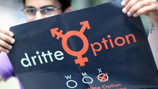 Vanja stands with a poster for a third option  in Leipzig, Germany, 30 August 2016. Vanja, aged 26, is intersex - neither man nor woman. Since 2014 Vanja and the support campaign 'Dritte Option'(third option)have been fighting for the introduction of a third gender - as yet unsuccessful. On 02 September 2016 they are submitting a constitutional complaint to the constitutional court in Karlsruhe. Photo:JANWOITAS/dpa