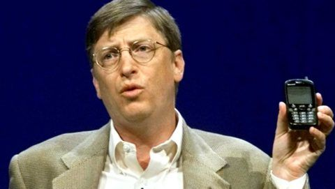 """Bill Gates, Chairman and Chief Software Architect of Microsoft, holds a new generation cell phone during his annual """"state of the industry"""" speech at the COMDEX convention in Las Vegas, Nevada,12 November, 2000. Gates outlined the sweeping changes he sees in computing and gave a blueprint of his vision for the next generation of the Internet.   AFP PHOTO/ Jeff CHRISTENSEN / AFP PHOTO / JEFF CHRISTENSEN"""