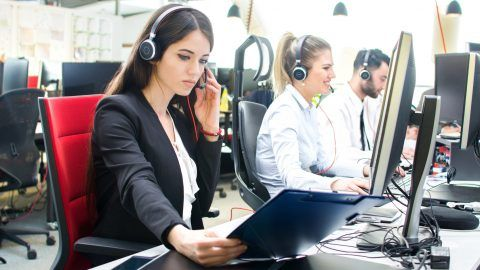 Young businesswoman working with a headset and accompanied by her team in call center.
