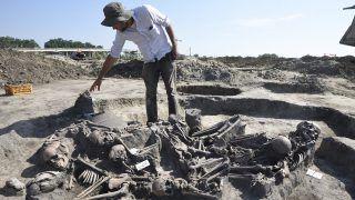 Hódmezővásárhely, 2017. június 28.Pópity Dániel, a szegedi Móra Ferenc Múzeum régésze mutatja a feltárt, tizenegy ember maradványait rejtő késő bronzkori, kora vaskori sírt Hódmezővásárhely-Kopáncs térségében egy homokbánya területén 2017. június 28-án. Az eltérő időpontokban életüket vesztő tizenegy embert valamilyen sajátos rítus részeként később együtt temették el újra.MTI Fotó: Kelemen Zoltán Gergely