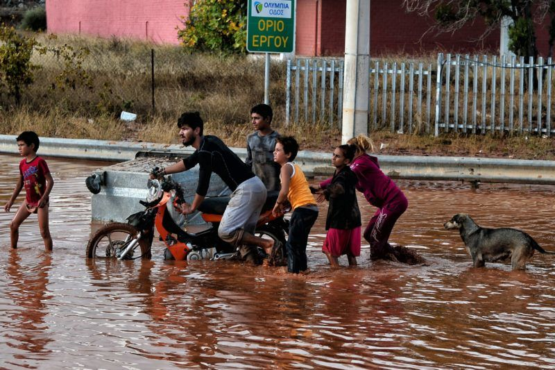 Mandra, 2017. november 15. Vízben gázoló helybeliek a heves esõzések által elöntött utak egyikén az Athén közelében fekvõ Mandrában 2017. november 15-én. A régióban pusztító viharok következtében legkevesebb hét ember életét vesztette. (MTI/EPA/Vaszilisz Pszomasz)