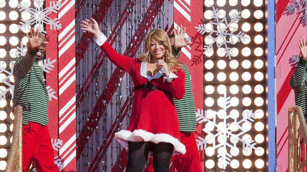 "LAKE BUENA VISTA, FL - DECEMBER 03:  In this handout photo provided by Disney, Grammy Award-winning singer Mariah Carey waves to the crowd in front of an oversized Christmas card while taping the ""Disney Parks Christmas Day Parade"" TV special at the Magic Kingdom on December 3, 2010 in Lake Buena Vista, Florida..  Carey performs two songs -- ""Oh Santa"" and ""All I Want For Christmas is You"" -- in the annual holiday telecast that airs Dec. 25, 2010 on ABC-TV.  (Photo by Matt Stroshane/Disney via Getty Images)"