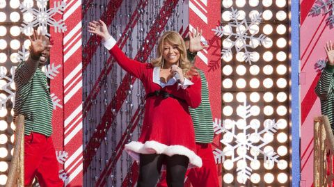 """LAKE BUENA VISTA, FL - DECEMBER 03:  In this handout photo provided by Disney, Grammy Award-winning singer Mariah Carey waves to the crowd in front of an oversized Christmas card while taping the """"Disney Parks Christmas Day Parade"""" TV special at the Magic Kingdom on December 3, 2010 in Lake Buena Vista, Florida..  Carey performs two songs -- """"Oh Santa"""" and """"All I Want For Christmas is You"""" -- in the annual holiday telecast that airs Dec. 25, 2010 on ABC-TV.  (Photo by Matt Stroshane/Disney via Getty Images)"""