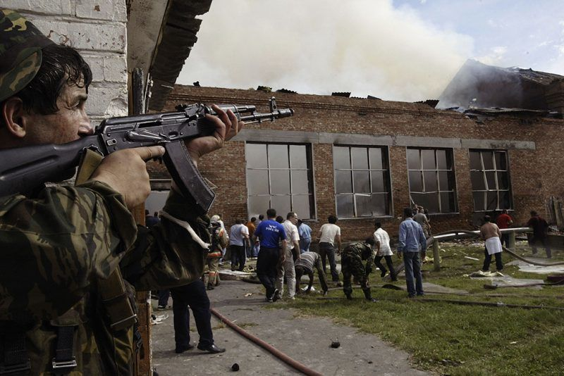 BESLAN, RUSSIA - SEPTEMBER 3:  A soldier covers the roof as volunteers survey the area after special forces stormed a school seized by Chechen separatists on September 3, 2004 in the town of Beslan, Russia. Unconfirmed reports state that at least 100 bodies have been discovered inside the school which was taken by Chechyen seperatists on September 1, the beginning of the russian school year.  (Photo by Oleg Nikishin/Getty Images)