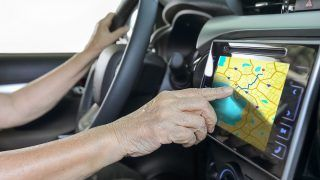 Elderly woman using GPS navigation system in car