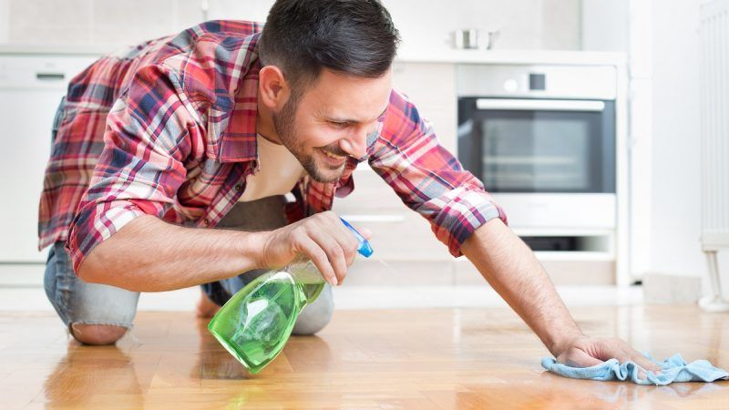 Happy handsome man wiping parquet floor and smiling. Husband housekeeping and cleaning concept. Home interior and kitchen in background