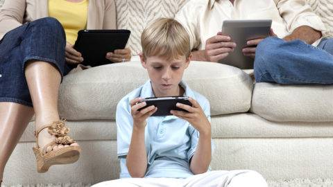 Boy and parents sit with hand-held devices