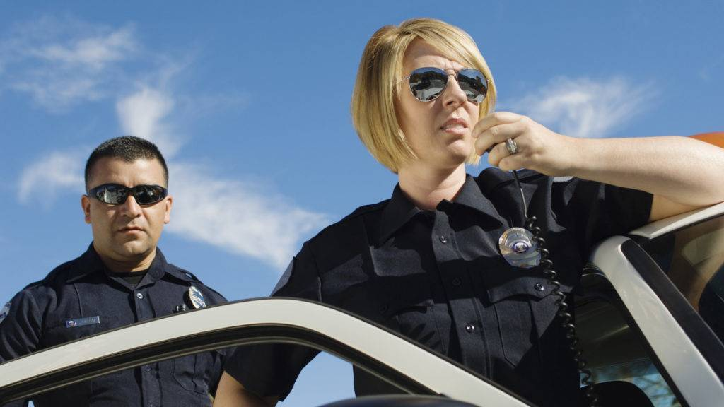 Low angle view  of a female police officer communicating on walkie-talkie with coworker in the background against sky