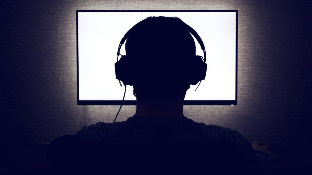 Man in headphones sits in front of a blank monitor in dark room