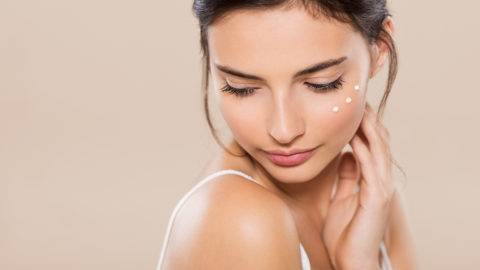 Young woman looking down with face moisturizer near eyes. Beautiful woman applying face lotion on her cheek. Beautiful intimate brunette girl with perfect and healthy skin feeling shy isolated on warm background.