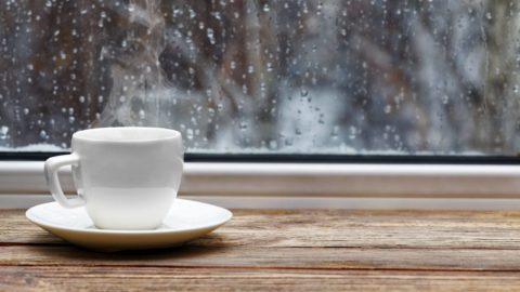 White steaming cup of hot tea or coffee on vintage wooden windowsill or table against window with raindrops on blurred background. Shallow focus.