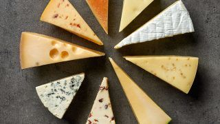 various types of cheese on black kitchen table, top view