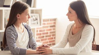 Troubled teenage girl and her mom are looking at each other and talking while sitting at home