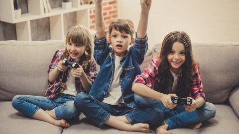 Cheerful kids are sitting together on sofa at home. Girls are playing game console while boy is cheering for them