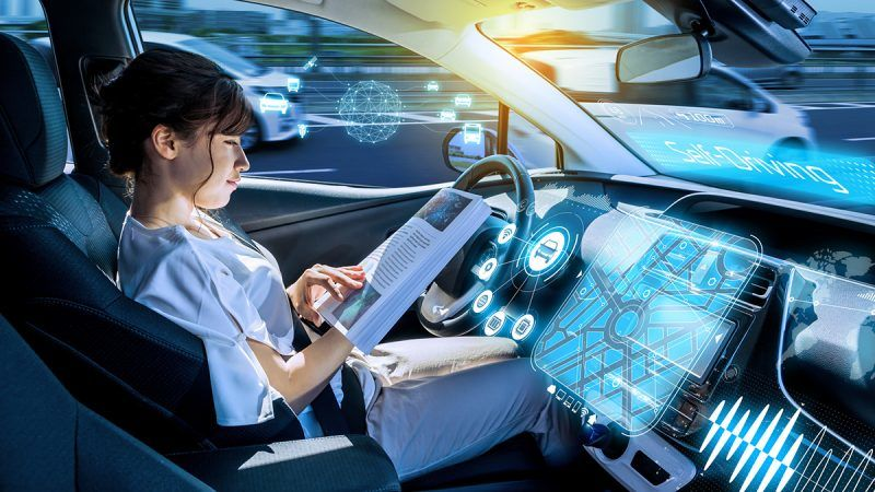 young woman reading a magazine in a autonomous car. driverless car. self-driving vehicle. heads up display. automotive technology.