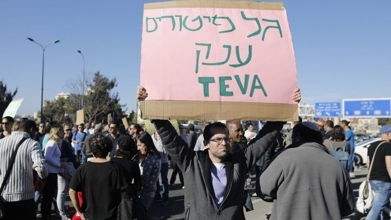 Israeli employees of Teva, the world's biggest manufacturer of generic drugs, hold placards during a protest in the centre of Jerusalem on December 17, 2017, against plans by the pharmaceutical giant to shed employees. Teva will make 1,750 employees redundant in Israel as part of plans to slash 14,000 jobs globally over two years, according to Histadrut trade union's head Avi Nissenkorn.  / AFP PHOTO / MENAHEM KAHANA