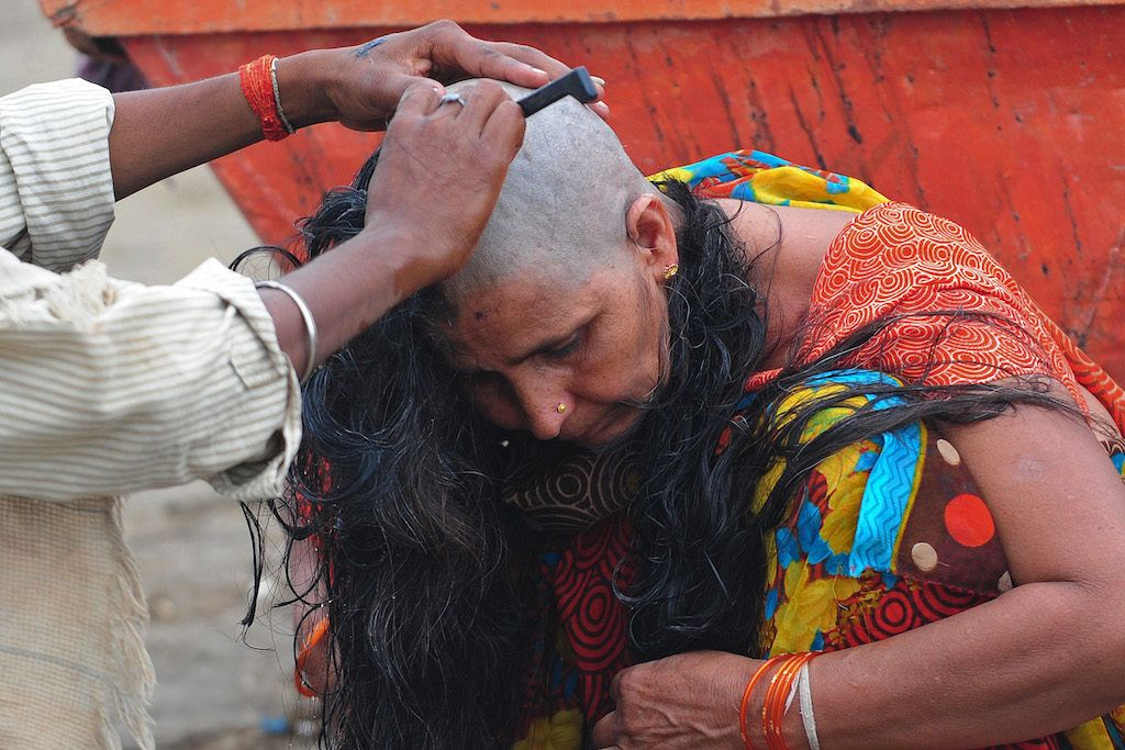 A barber shaves the head of a female devotees as part of a ritual where believers donate their hair at the Sangam in Allahabad on June 27, 2013. Devotees believe that donating hair gives liberation to humankind. AFP PHOTO/ SANJAY KANOJIA / AFP PHOTO / Sanjay Kanojia