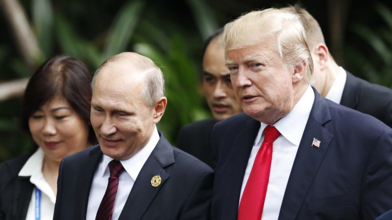 """US President Donald Trump (R) and Russia's President Vladimir Putin walk together to take part in the """"family photo"""" during the Asia-Pacific Economic Cooperation (APEC) leaders' summit in the central Vietnamese city of Danang on November 11, 2017. World leaders and senior business figures are gathering in the Vietnamese city of Danang this week for the annual 21-member APEC summit. / AFP PHOTO / POOL / JORGE SILVA"""