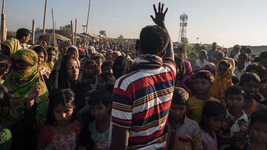 A man gestures telling Rohingya migrants queuing to recieve aid that the delivery has been cancelled, at the Kutupalong refugee camp at Cox's Bazar on November 30, 2017. Rohingya are still fleeing into Bangladesh even after an agreement was signed with Myanmar to repatriate hundreds of thousands of the Muslim minority displaced along the border, officials said on November 27.  / AFP PHOTO / Ed JONES