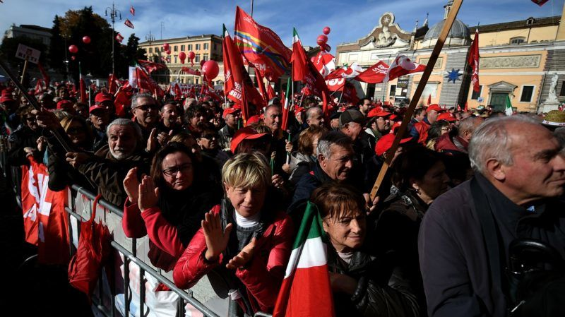Demonstrators of Italian biggest trade-union confederation, leftwing CGIL, wave flags of the trade-union as they gather to protest against the reforms concerning the pension policy and in particular the automatic rise of the pension age to 67 by 2019, during a demonstration at Piazza del Popolo, in Rome, on December 2, 2017. / AFP PHOTO / FILIPPO MONTEFORTE
