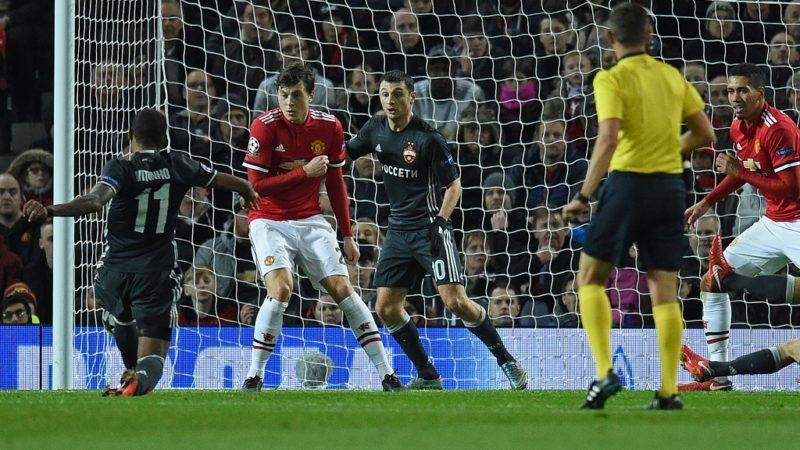 CSKA Moscow's Brazilian midfielder Vitinho (L) shoots towards CSKA Moscow's Russian midfielder Alan Dzagoev as the deflection creates the opening goal of the UEFA Champions League Group A football match between Manchester United and CSKA Moscow at Old Trafford in Manchester, north west England on December 5, 2017. / AFP PHOTO / Oli SCARFF