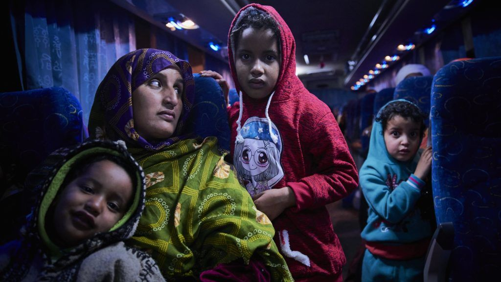 """A Malian migrant woman with her children is transferred by bus to a temporary shelter upon their arrival in Bamako on December 13, 2017, after being repatriated from Libya by the IOM (International Organisation for the Migrations).   Amnesty International on December 12, 2017 accused Italy and other European Union governments of being """"knowingly complicit"""" in horrific abuses of migrants in Libya, warning of legal action against them at European and UN rights institutions. Human-trafficking networks have flourished in the chaos that followed a NATO-backed uprising which toppled long-time Libyan dictator in 2011. / AFP PHOTO / MICHELE CATTANI"""