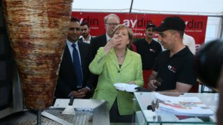 """BERLIN, GERMANY - JUNE 27: German Chancellor Angela Merkel cuts pieces of Turkish doner kebab during her visit to the 42nd summer fest of the parliamentary """"Working Committee for Mid-sized Enterprises"""" in Berlin, Germany on June 27, 2017. Erbil Basay / Anadolu Agency"""
