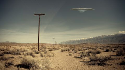 Low flying UFO spaceship hovering over a desert dirt road near a telephone pole with a vintage look.
