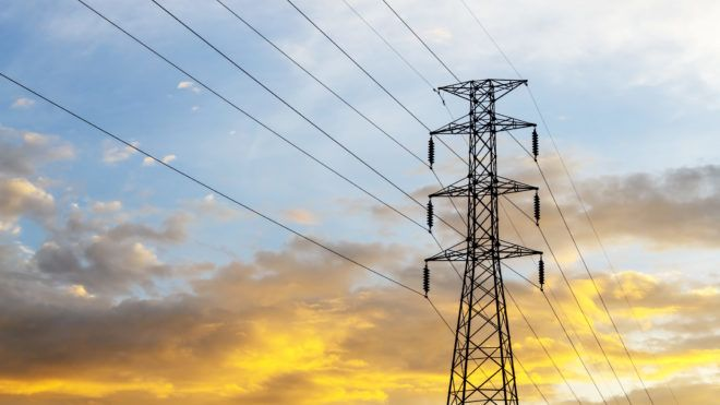 High voltage power lines with electricity pylons at twilight.