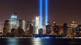 New York City downtown urban architecture at night and September 11 tribute light