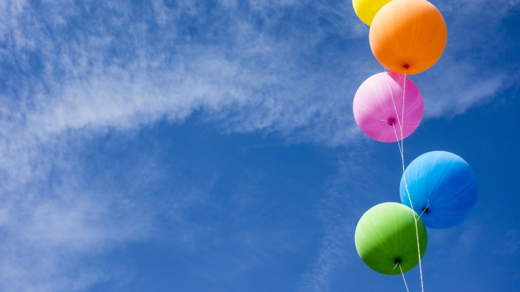 Colorful air balloons over blue sky background.