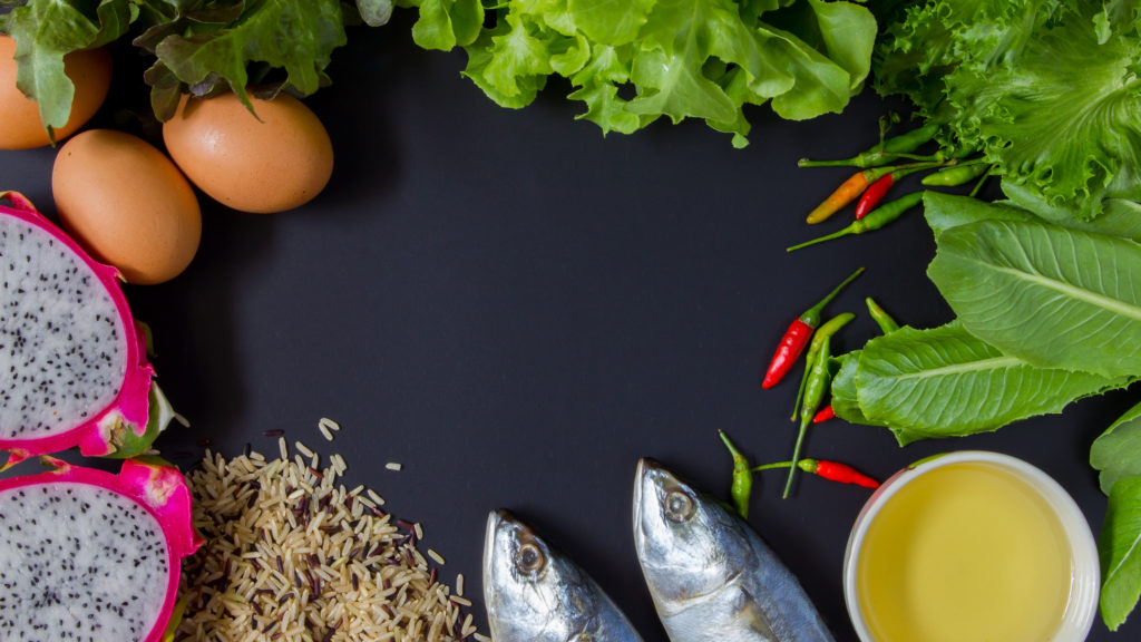 Fresh mackerel, fresh vegetables, rice, oil and fruits on chalkboard background. Concept about eating 5 groups.