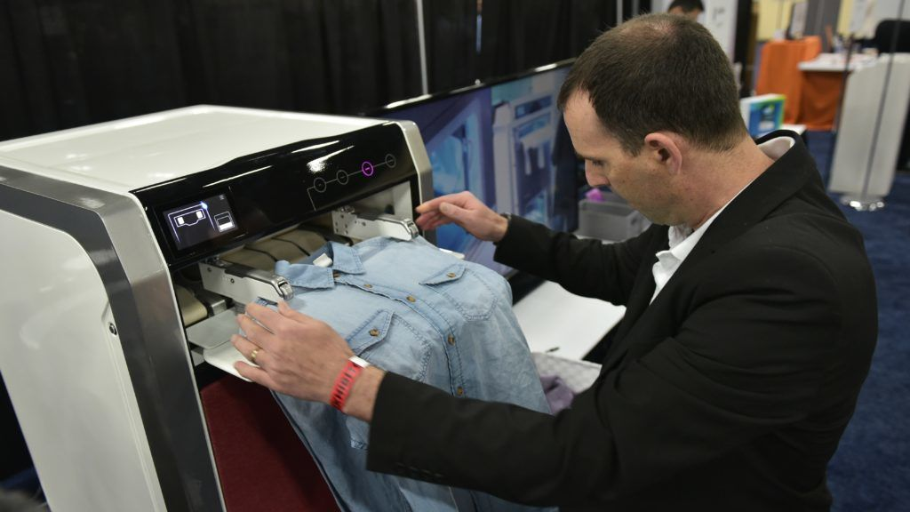 An exhibitor demostrates the FoldiMate laundry folding machine during the CES Unveiled preview event at the Mandalay Bay Convention Center during CES 2018 in Las Vegas on January 7, 2018. / AFP PHOTO / MANDEL NGAN