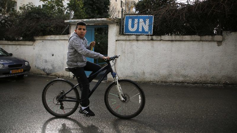 A Palestinian boy cycles past a United Nations' run health centre in the Qalandia refugee camp near Ramallah in the West Bank, on January 17, 2018 after the White House froze tens of millions of dollars in contributions. The UN agency for Palestinian refugees faces its worst funding crisis ever after the United States froze tens of millions of dollars in contributions, its spokesman said. / AFP PHOTO / ABBAS MOMANI