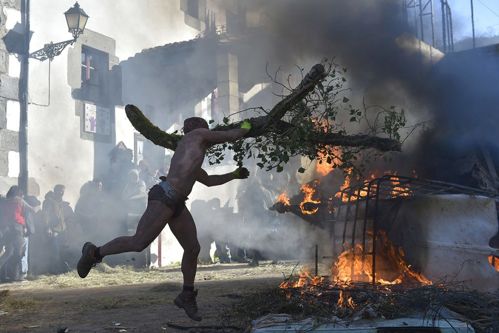 A masked participant throws a tree branch to a burning car during the ancient carnival of Zubieta, in the northern Spanish Navarra province on January 30, 2018. The yearly three day festivities, revolving mainly around agriculture and principally sheep hearding, run on the last Sunday, Monday and Tuesday of January where Navarra Valley locals from two villages dress up and participate in a variety of activites as they perform a pilgrimage through each village. / AFP PHOTO / ANDER GILLENEA