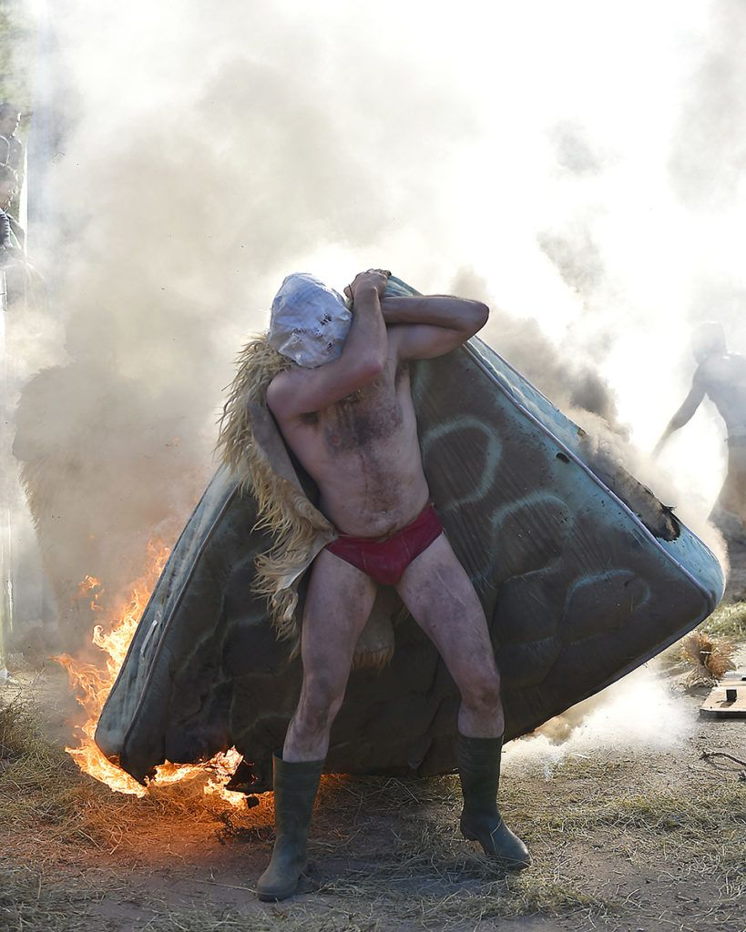A masked participant carries a burning matress during the ancient carnival of Zubieta, in the northern Spanish Navarra province on January 30, 2018. The yearly three day festivities, revolving mainly around agriculture and principally sheep hearding, run on the last Sunday, Monday and Tuesday of January where Navarra Valley locals from two villages dress up and participate in a variety of activites as they perform a pilgrimage through each village. / AFP PHOTO / ANDER GILLENEA