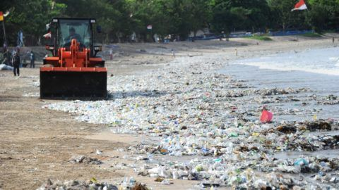 This photo taken on December 19, 2017 shows rubbish collectors using heavy equipment to clear plastic trash on Kuta beach near Denpasar, on Indonesia's tourist island of Bali. The palm-fringed shoreline of Bali's Kuta beach has long been a favourite with tourists seeking sun and surf, but nowadays its golden shores are being lost under a mountain of garbage. / AFP PHOTO / SONNY TUMBELAKA / TO GO WITH Indonesia-rubbish-Bali-environment,FEATURE by Bagus Saragih